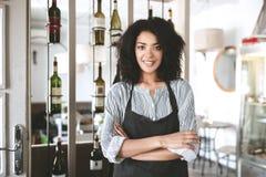 Mooi Afrikaans Amerikaans meisje in schort die zich met die wapens bevinden in restaurant worden gevouwen Jong meisje met donker  royalty-vrije stock foto's