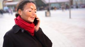 Mooi Afrikaans meisje die met vitiligo zich op de straat bevinden die mobiele telefoon en het glimlachen spreken stock footage