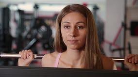 Mooi atletisch jong meisje die aan de bar voor hurkzit in de gymnastiek komen stock footage