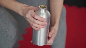 Mooi atletisch jong meisje die na klassen in de gymnastiek rusten en een fles water houden stock video