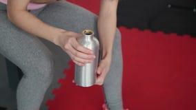 Mooi atletisch jong meisje die na klassen in de gymnastiek rusten en een fles water houden stock videobeelden