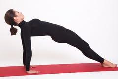 Mooi atletisch meisje in een zwart kostuum die yoga doen De plank van Purvottanasanaasana stelt Op witte achtergrond stock foto