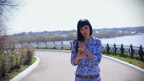 Mooi Aziatisch meisje in jeans die in de zomer in een park op een zonnige dag lopen en een bericht op een smartphone lezen stock video