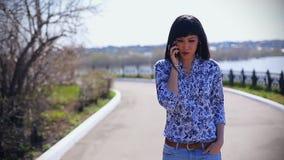 Mooi Aziatisch meisje in jeans die in de zomer in het park op een zonnige dag lopen en op de telefoon spreken stock video