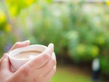 Mooi Aziatisch wijfje die een kop van koffie drinken bij de tuin stock afbeeldingen