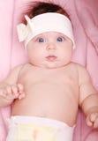 Mooi babymeisje die met boog in haar een gelukkige glimlach glimlachen Stock Afbeeldingen