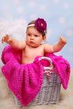 Mooi babymeisje in rieten mand, 10 maanden Stock Afbeelding