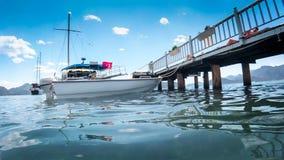 Mooi beeld van houten pijler met vastgelegd jacht en boten bij heldere zonnige dag royalty-vrije stock afbeelding