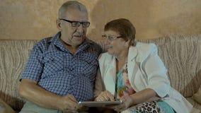 Mooi bejaard paar die foto's op uw tablet kijken stock video