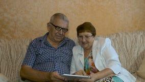 Mooi bejaard paar die foto's op uw tablet kijken stock footage