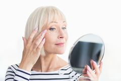 Mooi bejaarde die anti-rimpelroom toepassen, die spiegel houden royalty-vrije stock fotografie