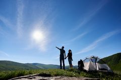 Mooi berglandschap onder blauwe hemel met heldere zon De kerel toont meisje van bergen stock foto