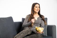 Mooi binnenlands meisje die spaanders eten, lettend op TV, die bij bank op wit zitten Royalty-vrije Stock Foto's