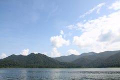 Mooi blauw hemelberg en water stock afbeeldingen