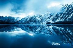 Mooi blauw meer in de bergen Vlakke spiegeloppervlakte van het water onder de wolken royalty-vrije stock afbeeldingen