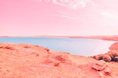 Mooi blauw meer op de achtergrond van koraalkust en roze hemel stock afbeelding