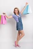 Mooi blond meisje in denimoverall en een purper overhemd die multicolored het winkelen zakken houden het gelukkige meisje gaat wi stock foto