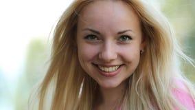 Mooi blond meisje die met perfecte huid bij camera, zonnebril glimlachen weg en stock videobeelden
