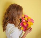 Mooi blond meisje in het blauwe boeket van de kledingsholding van gele en roze rozen op een lichtgele achtergrond stock afbeeldingen