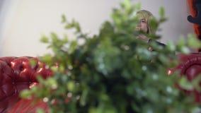 Mooi blond meisje in zwarte kleding en zwarte nylonkousen die op de telefoon op speakerphone spreken stock footage