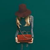 Mooi blond model in modieuze rode hoed en een rode koppeling op gr. Stock Foto's