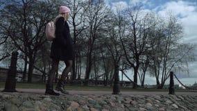 Mooi blond tienermeisje die op de stoep rond park lopen Zij is jongelui stock videobeelden
