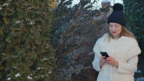 Mooi blonde in bontjasoverseinen bij smartphone bij sparrenachtergrond stock footage
