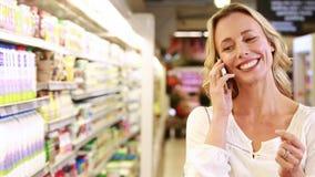 Mooi blonde die een telefoongesprek maken terwijl het winkelen stock video