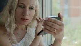 Mooi blonde die haar make-up in de spiegel bekijken stock videobeelden