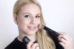 Mooi blonde die op make-up zetten Stock Foto's