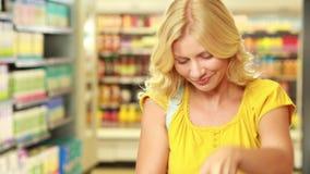 Mooi blonde die product in karretje zetten stock video