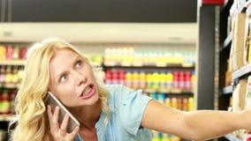 Mooi blonde die product zoeken terwijl het telefoneren stock video