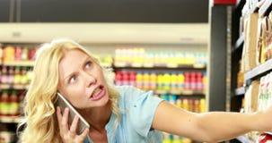 Mooi blonde die product zoeken terwijl het telefoneren stock footage