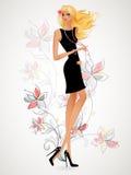 Mooi blonde in een zwarte kleding die zich op achtergrondflo bevinden Royalty-vrije Stock Foto's