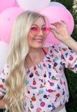 Mooi blonde in glazen in de vorm van een hart, tegen een achtergrond van ballons Blije emoties viering royalty-vrije stock fotografie