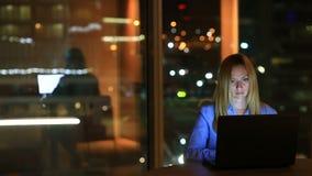 Mooi blonde het bedrijfsvrouw werk overwerk bij nacht in uitvoerend bureau De stadslichten zijn zichtbaar op achtergrond stock videobeelden