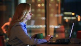 Mooi blonde het bedrijfsvrouw werk overwerk bij nacht in uitvoerend bureau De stadslichten zijn zichtbaar op achtergrond stock footage