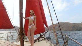 Mooi blonde in het witte bikini ontspannen op een jacht op zee stock footage