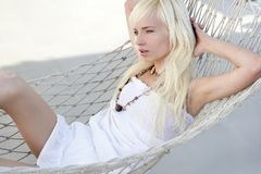 Mooi blonde jong meisje dat op hangmat wordt ontspannen Stock Fotografie