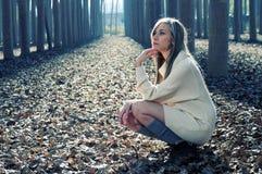 Mooi blonde meisje dat in het hout denkt Stock Fotografie