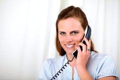 Mooi blonde meisje dat op telefoon glimlacht Royalty-vrije Stock Foto's