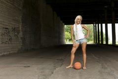 Mooi blonde meisje dat zich met basketbal bevindt Royalty-vrije Stock Afbeeldingen