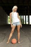 Mooi blonde meisje dat zich met basketbal bevindt Stock Afbeelding