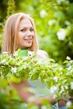 Mooi blonde meisje in de tuin Stock Afbeelding