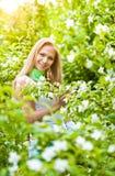 Mooi blonde meisje in de tuin op een zonnige dag Royalty-vrije Stock Fotografie