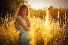 Mooi blonde met een lang krullend haar in een lange avondjurk in motie in openlucht in aard in de zomerzonsondergang Royalty-vrije Stock Foto's