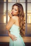 Mooi blonde met een lang krullend haar in een lange avondjurk in statisch in openlucht dichtbij retro uitstekende bouw in de zome Stock Afbeeldingen