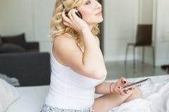Mooi blonde met grote borsten in witte T-shirt en nachtborrelsontwaken in de ochtend, die aan muziek luisteren stock foto's