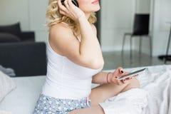 Mooi blonde met grote borsten in witte T-shirt en nachtborrelsontwaken in de ochtend, die aan muziek luisteren royalty-vrije stock afbeeldingen
