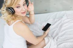 Mooi blonde met grote borsten in witte T-shirt en nachtborrelsontwaken in de ochtend in haar bed, die luisteren aan stock afbeeldingen